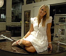 Model Charlotte Meares seatting on the counter of her Pedini kitchen